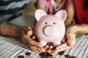 Photo of person holding piggy bank of cash